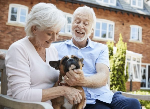 Two older adults playing with a dog